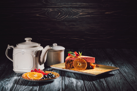 carrot cake with berry filling on plate, orange slices, blueberries and cranberries on saucer near teapot on wooden table Stock Photo