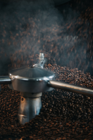 Steaming hot coffee beans being roasted in professional machine Stock Photo