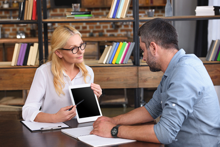 female counselor pointing on digital tablet with blank screen by pen to male patient at table in office Stock Photo