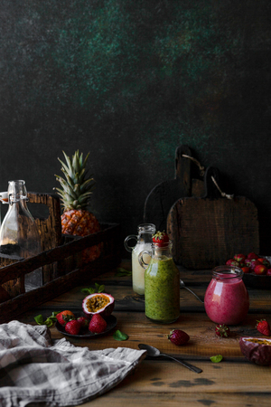Organic fruit smoothies with fruits in mess on wooden background