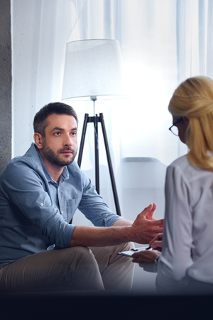 man gesturing and talking to female counselor while she writing in clipboard at office