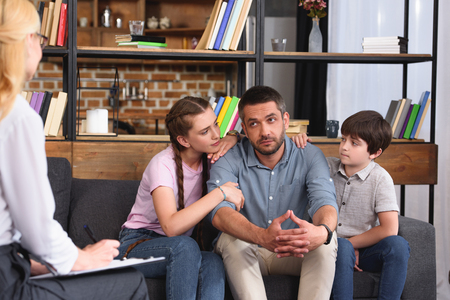 children cheering up father while he talking to female counselor on therapy session Stock Photo