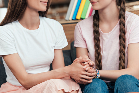 cropped image of daughter holding hands of mother while sitting on sofa Stock Photo
