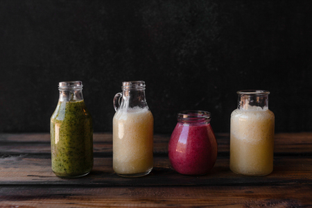 Set of bottles with fresh healthy smoothies on rustic table