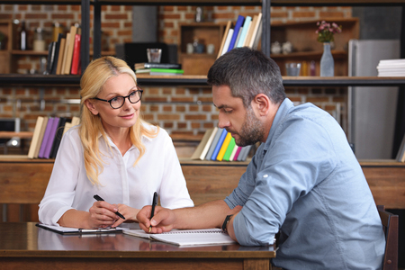 side view of man writing in textbook while female counselor talking to him at office Stock Photo