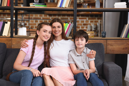 smiling mother embracing teenage daughter and little son on sofa at home