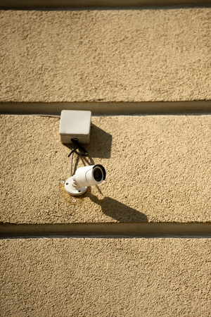 closeup shot of security camera on building facade in sunlight