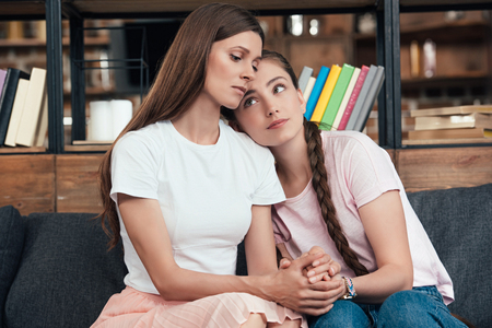 careful teenage girl laying on shoulder of frustrated mother on sofa at home Stock Photo