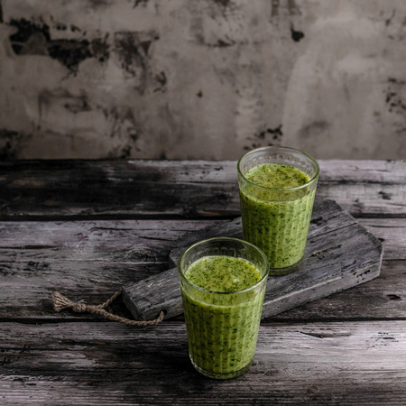 Organic green smoothie in glasses on wooden table Stock Photo