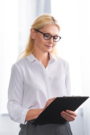 mature female therapist in eyeglasses writing in clipboard Stockfoto