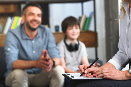 cropped image of female counselor writing in clipboard while father and son sitting on therapy session
