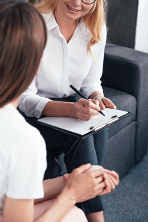 cropped image of woman talking to female counselor while she writing in clipboard at office