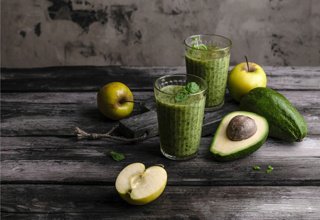 Green detox smoothie with avocado on rustic wooden board Stock Photo