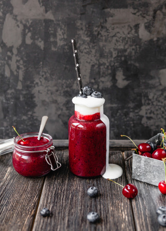 Delicious detox smoothie in bottle and jar on rustic wooden board Stock Photo