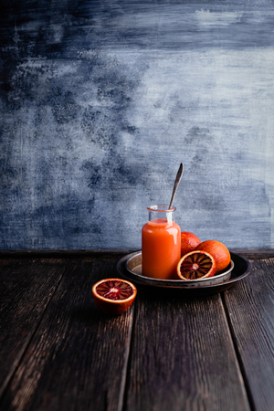 Delicious detox smoothie on rustic wooden board with blood oranges