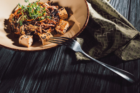 high angle view of soba with tofu and vegetables decorated with germinated seeds of sunflower on plate near kitchen towel and fork on wooden table