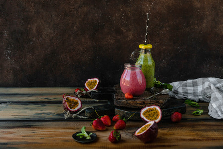 Fresh healthy smoothies on rustic table with berries and passion fruit Stock Photo