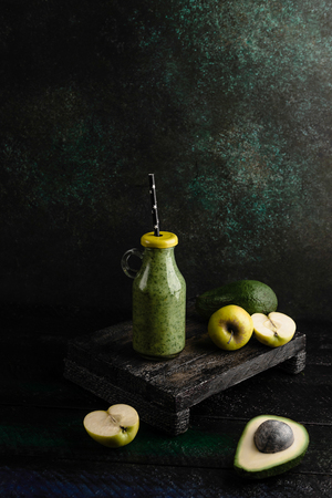 Organic fruit smoothie with avocado and apples on wooden background
