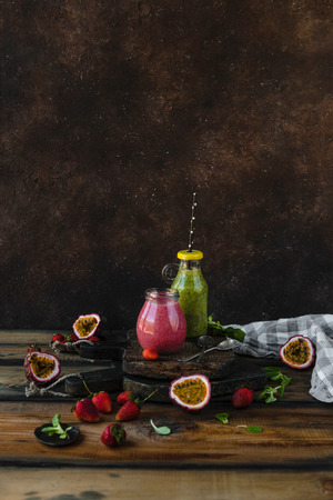 Berry healthy smoothies on rustic table with passion fruit