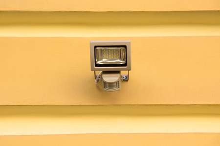 close up view of spotlight lamp on yellow building facade