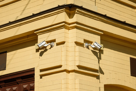closeup image of security cameras on yellow building facade in sunlight Stock Photo