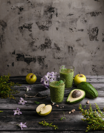 Organic fruit smoothie on wooden background with fruits and flowers