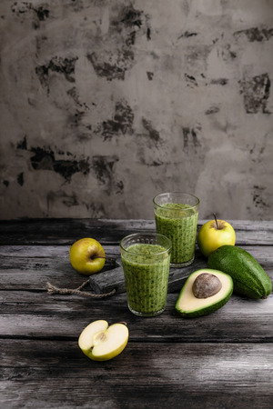 Fresh healthy smoothie on rustic table with apples and avocado