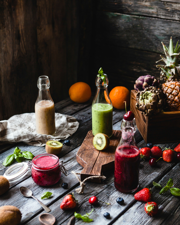 Fresh healthy smoothies in glass bottles on rustic table with assorted fruits