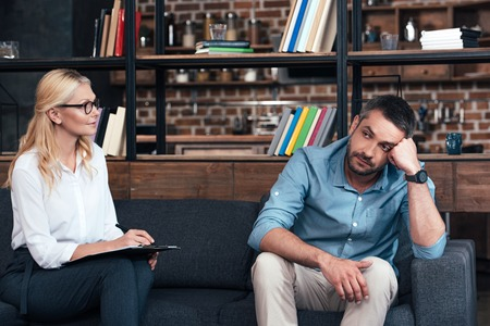 female counselor writing in clipboard and talking to frustrated man during therapy session in office