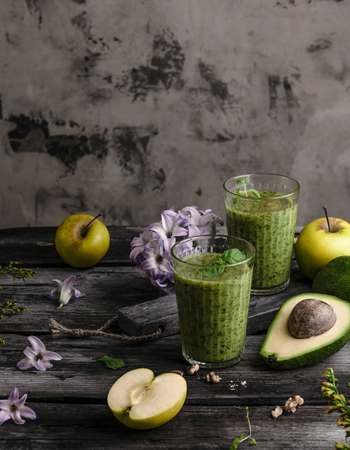 Delicious detox smoothie on rustic wooden board with fruits and flowers Stock Photo