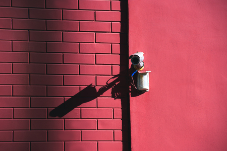 close up view of security camera on pink building facade in sunlight