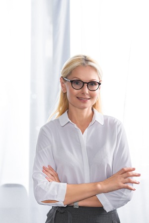 portrait of female therapist in eyeglasses with crossed hands