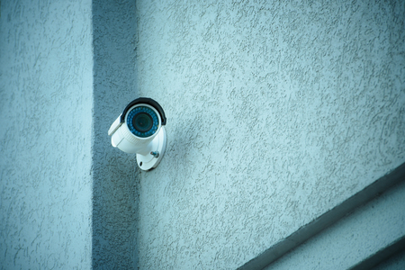 close up view of security camera on gray building facade Stockfoto