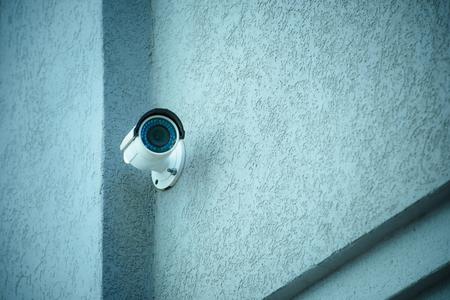 Vista de cerca de la cámara de seguridad en la fachada del edificio gris