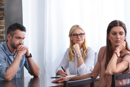 woman turned away and her frustrated husband sitting at table on therapy session by female counselor in office Stock Photo