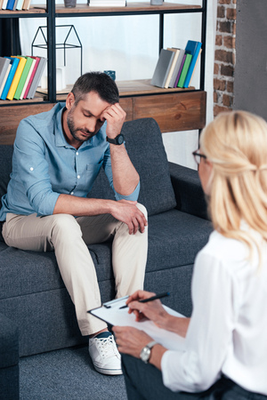 depressed man sitting on sofa while female psychiatrist writing in clipboard at office