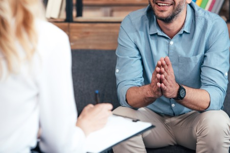 cropped image of female counselor writing in clipboard and smiling male holding hand palms together during therapy session in office Stock Photo