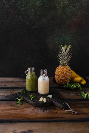 Delicious detox smoothies with tropical fruits on rustic wooden board Stock Photo