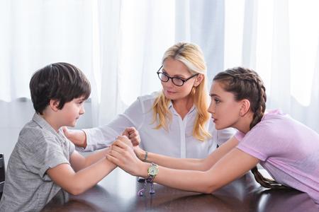 Vue latérale de l'adolescente tenant par la main du petit frère et une conseillère lui remontant le moral au bureau