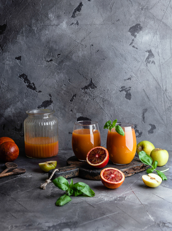 Organic fruit smoothie on wooden background with oranges and apples