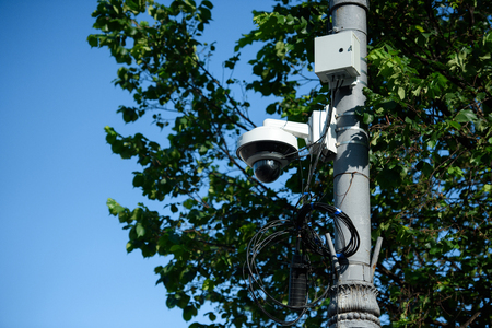close up view of security camera on street pole with tree foliage in sunlight Stock Photo