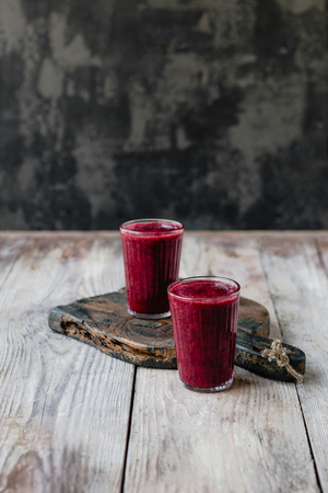 Delicious detox blueberry smoothie in glasses on rustic wooden board