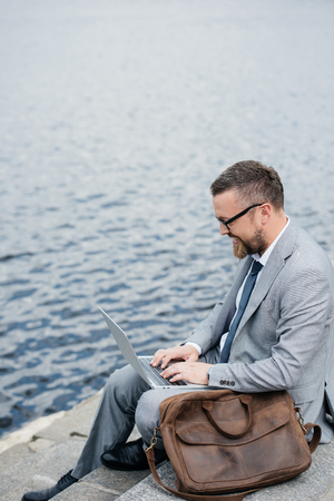 businessman using laptop and sitting on quay with leather bag Stock Photo