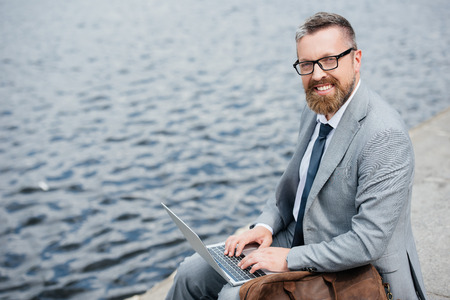 handsome businessman using laptop and sitting on quay with leather bag