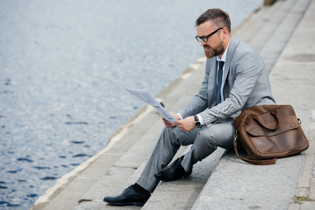 handsome businessman in grey suit with leather bag reading newspaper on quay