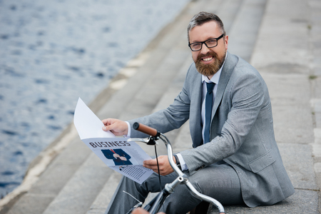 handsome smiling businessman in grey suit reading newspaper on quay with bicycle