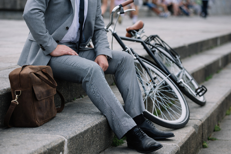 cropped view of businessman in grey suit sitting on stairs with bike Reklamní fotografie