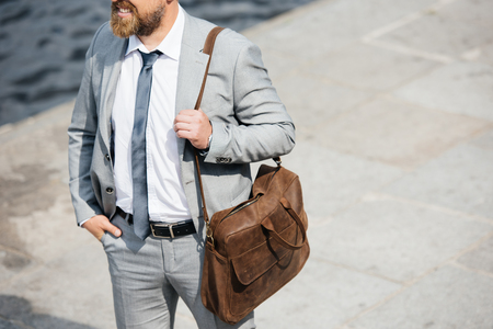 cropped view of businessman with leather bag walking on quay