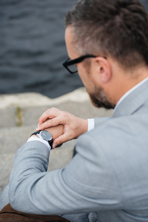 back view of businessman in grey suit looking at watch Stockfoto