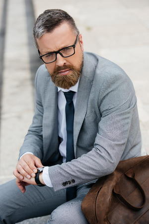 handsome bearded businessman in grey suit with leather bag and watch